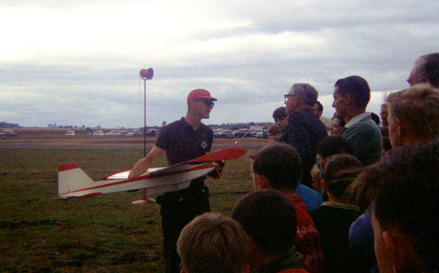 An image of a man holding his RC model aircraft while answering questions from onlooking spectators