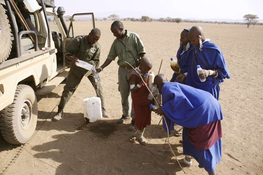 A Paul Augustinus image of several blue robed Masai women getting water from our guides next to the vehicle .