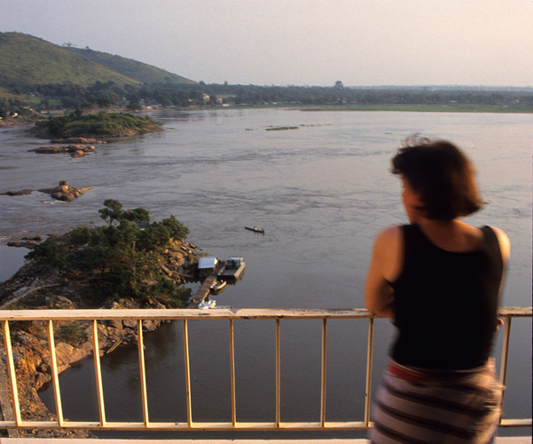 An image of Clarissa Augustinus looking out from a balcony high above a very wide river.