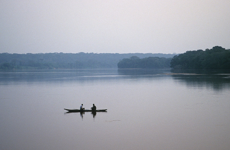An image of the huge sheet of water that is the Sangha River. In the middle ground, a solitary dugout with two passengers slowly drights along with the current.