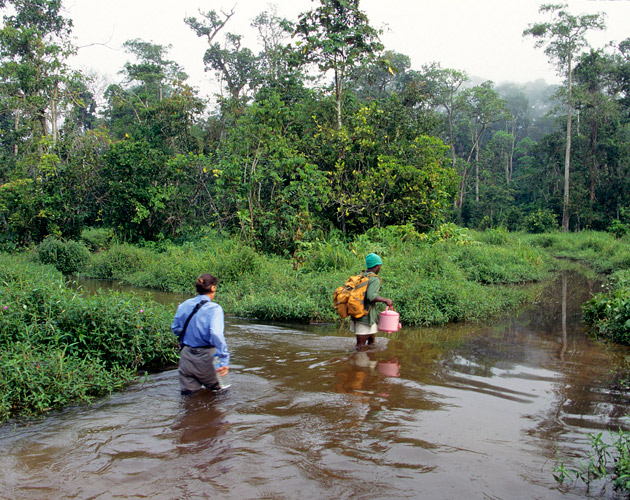 An image of Clarissa and guide wading through waist deep water while crossing a stream.
