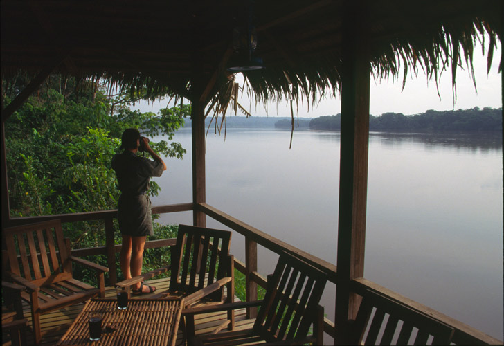 An evening image taken by Paul Augustinus of his wife Clarissa looking out over the vast width of the Sangha River from the rustic wooden balcony of Doli Lodge.