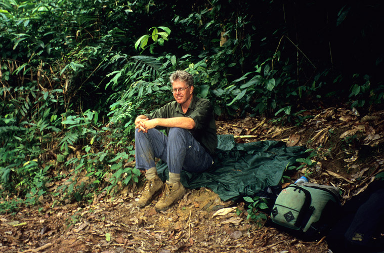 An image of a smiling, sweaty but tired looking Paul Augustinus sitting on the forest floor during a break from the hike in to Dzangha.