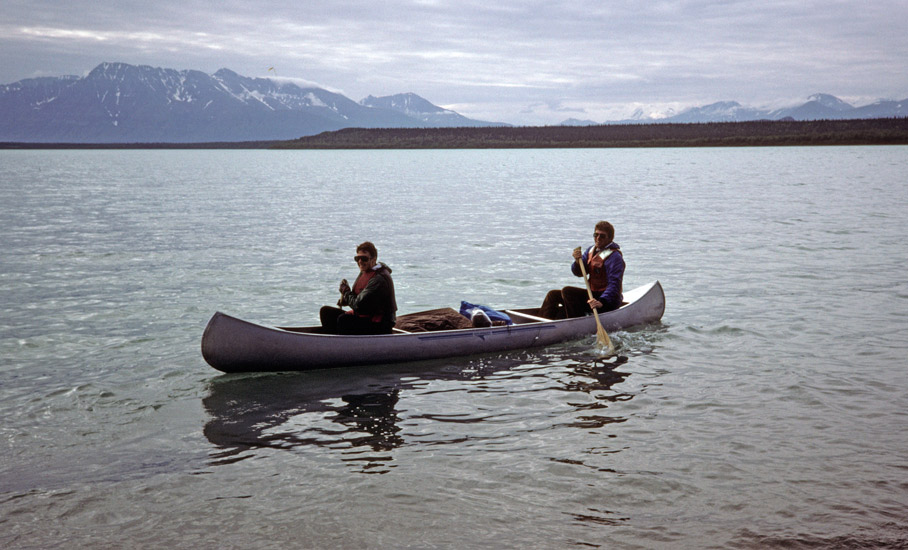An image of Paul and Clarissa Augustinus in their canoe prior to setting off. In the background is the vast expanse of a frigid Alaskan glacial lake.