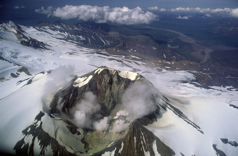 An aerial image of  a volcanic cone in the Alaska Range in the region where Paul Augustinus was camped. It is still active and the snow is tinged yellow with sulphurous deposits.