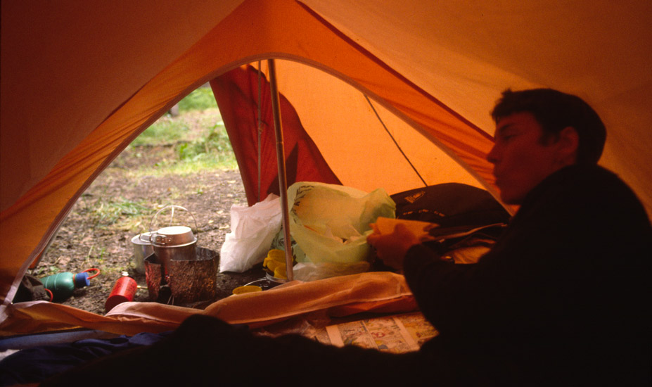 An image of Clarissa Augustinus inside the entrance of the small tent eating the supper we had heated up on a small white spirit camping stove.