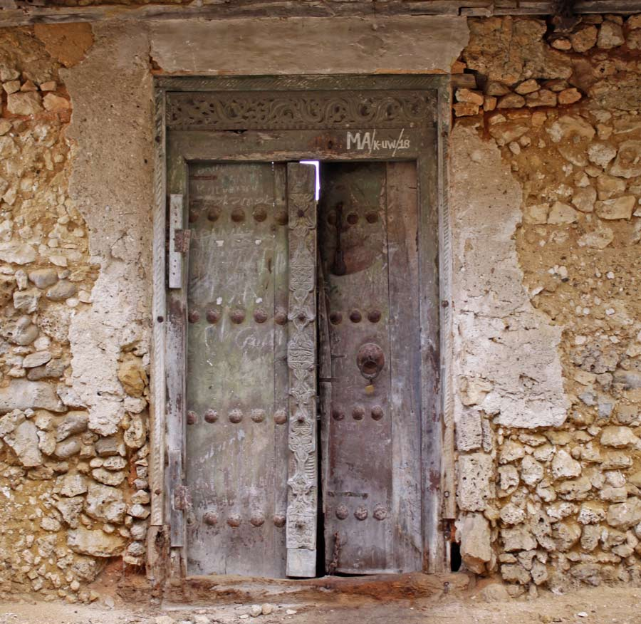 An image of  a run down building in a bad state of disrepair, that has a beautifully carved Zanzibar Door.