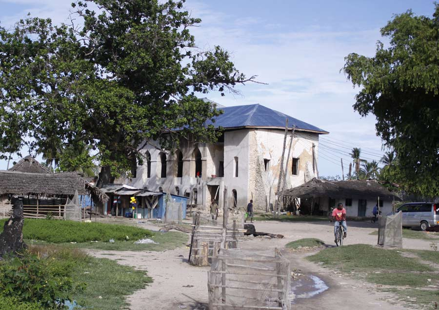 An image of a run down two-storey building set in a rustic coastal village location.