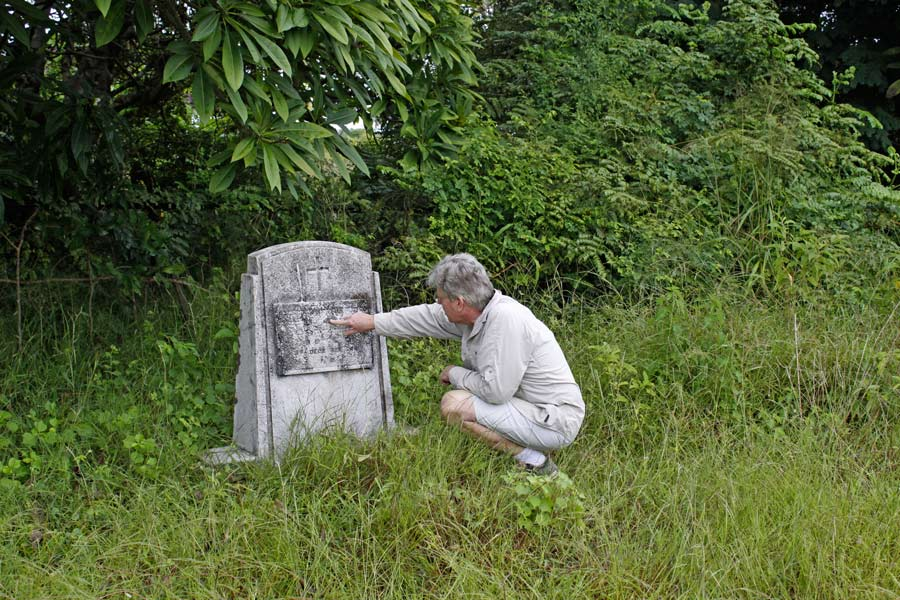 An image of Paul Augustinus examining an old German war grave in an overgrown fiels.