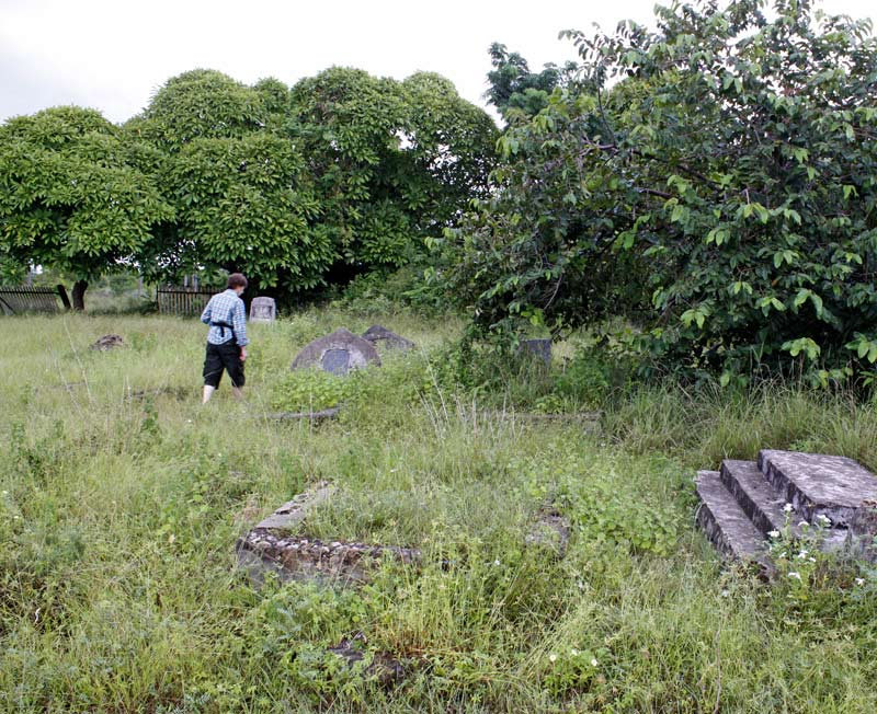 An image of Clarissa Augustinus walking through the overgrown graveyard at Kilwa.