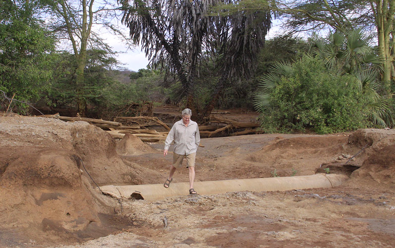 An image of Paul Augustinus walking over an exposed segnent of the piple from Mzima Springs that takes water to Mombasa.
