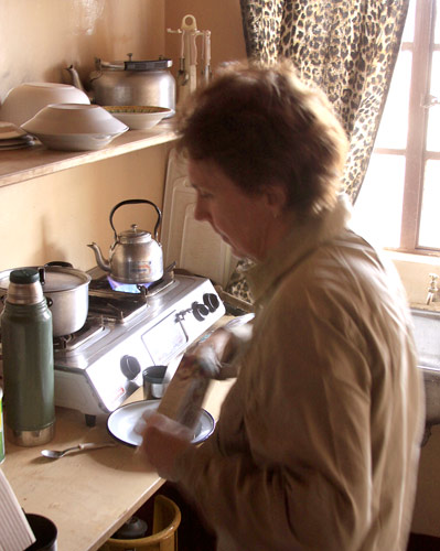 An image of Clarissa Augustinus in the simple rustic kitchen preparing a meal.