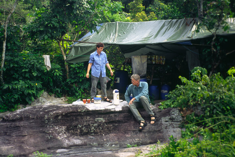 An image of Paul and Clarissa Augustinus having a meal outside of the store tent at the camp. Again they are sitting on the rocks.