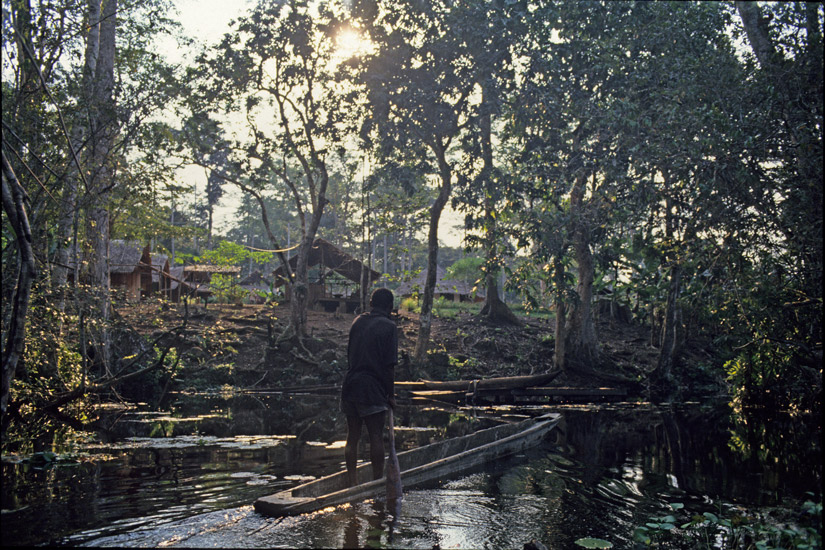 An image of  a tiny village on the edge of a stream inside the rainforest. In the foreground is a pirogue with its poler heading towards the landing point.