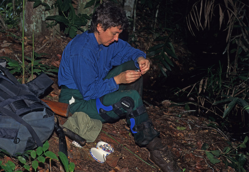 An image of Clarissa Augustinus sitting by a path, and eating a small lunch of cheese and nuts. On her leg is the brace she had to wear for the entire trip because of the injury she sustained in a gym the week before we traveled.