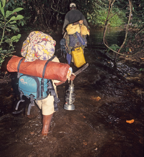 An image of porters carrying camping gear while wading through a stream in the dark.