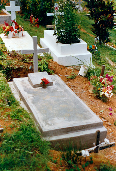 An image of a freshly made grave with a neat white painted concrete cap and cross with the small plaque at the head