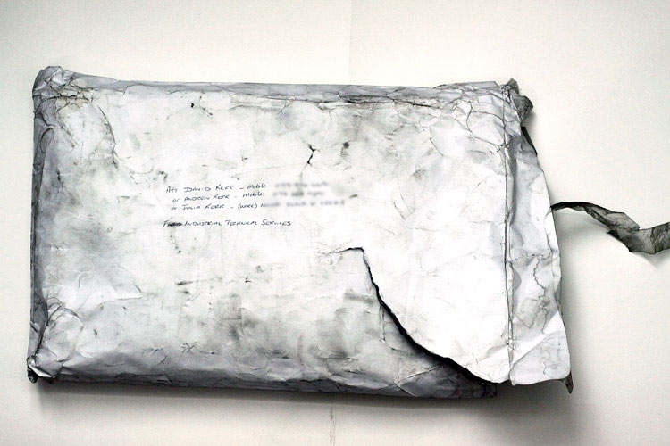 A Paul Augustinus  image of a weather-beaten, grubby, A3 sized package, which is quite obviously filled with documents and other stuff as it has burst open at the top and been taped up again. On the front is the Nairobi phone number of David Kerr and their son which Jackie had written many years previously