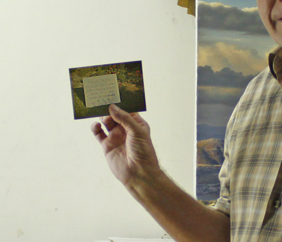 An image of Paul Augustinus holding up a small postcard sized photo of a white marble plaque with his fathers name on it