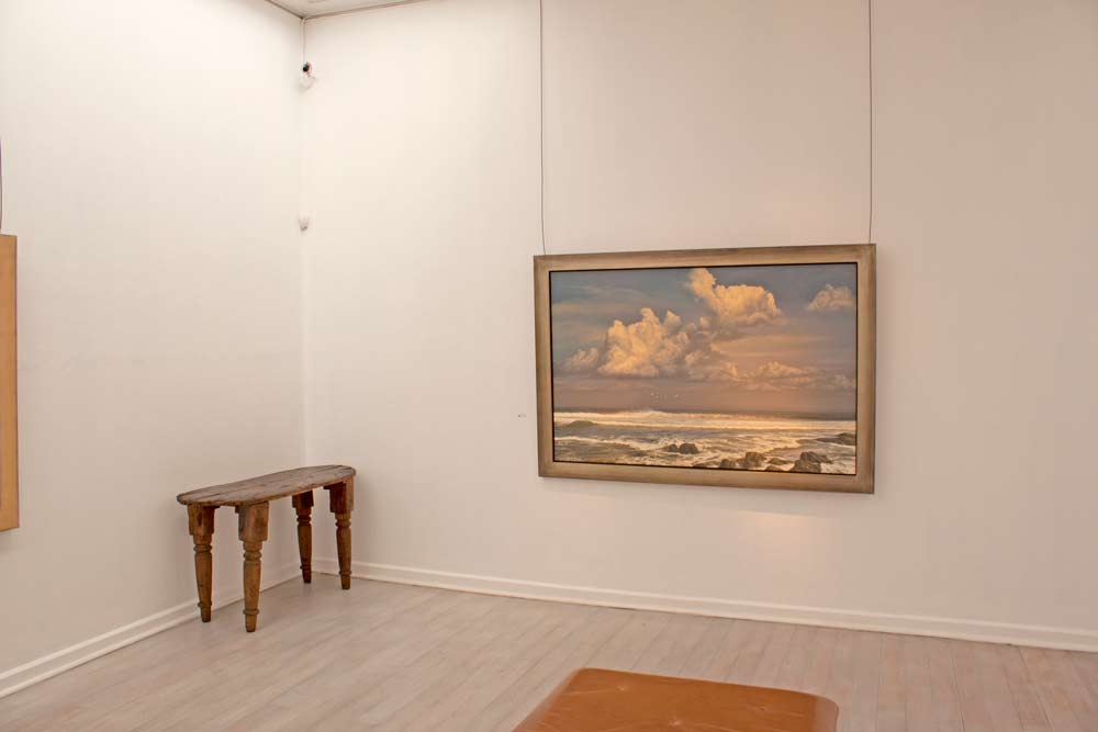A framed Paul Augustinus painting hanhs on a plain white wall in an elegant gallery space.